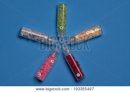 Closeup set of colorful nail makeup glitters in bottle isolated on blue background. Concept of beauty and makeup