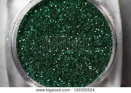 Closeup of green nail makeup glitter in round jar isolated on silver background. Concept of beauty and makeup