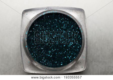 Closeup of teal nail makeup glitter in round jar isolated on silver background. Concept of beauty and makeup