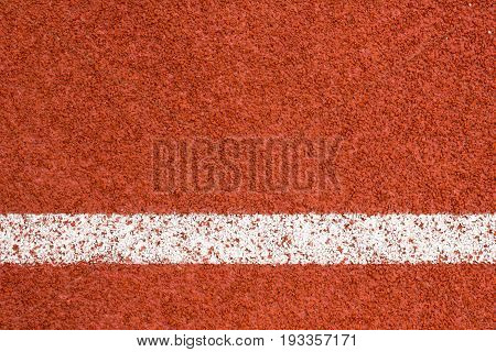 Running track with white striped on redbrick color background.