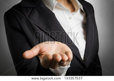 business woman in black suit open palm hand for show something.