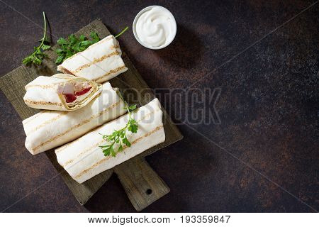 Shawarma Pita Bread With Grilled Chicken, Fresh Vegetables And Cream Sauce On A Background Of Brown