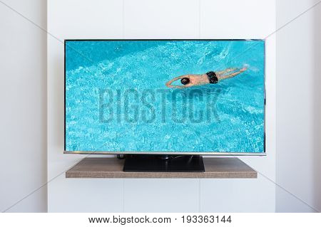 TV television Man swimming pool on screen white wall background. with clipping path