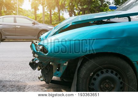 Front of green car got damaged by accident on the road.