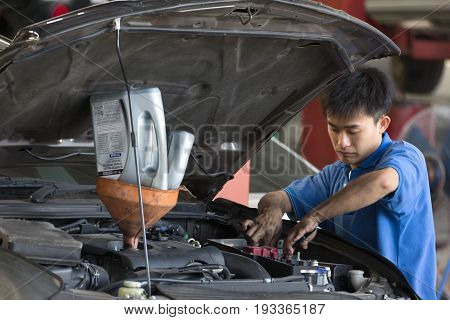 Bangkok Thailand - March 08, 2018 : Automobile Mechanic Examining Car Suspension Of Lifted Automobil
