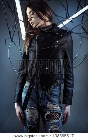 elegant robot girl in wires in style cyberpunk in leather jacket and ripped jeans