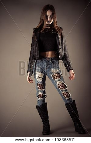 fashionable teenager girl in leather jacket and torn jeans
