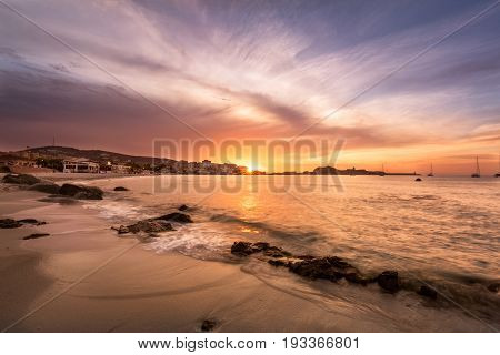 Dramatic sunset over the beach at L'Ile Rousse in the Balagne region of Corsica with rocks in the foreground bars and restaurants along the front and the red rock port and lighthouse in the distance