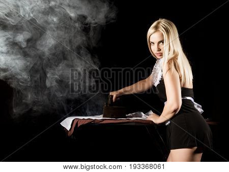 sexy blonde woman in housekeeper suit, ironing white shirt with old iron. retro style. housewife concept