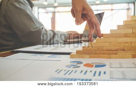 Concept walking his fingers up wooden steps on the way to success.