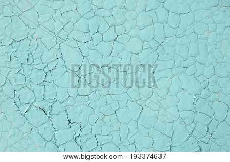 The texture of the turquoise paint on the metal surface