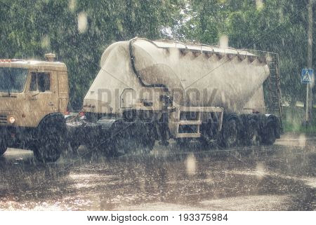 Large truck with a trailer on the road under heavy rainfall.