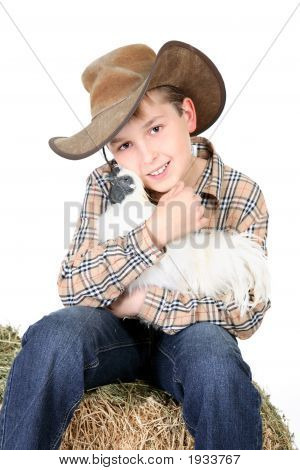 Boy sitting on a lucerne bale and holding a bantam chicken poster