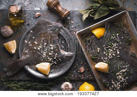 Cooking flounder with seasoning on the stone background top view horizontal