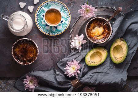 Catalan cream , cup of coffee , milk , avocado and flowers on the stone background top view