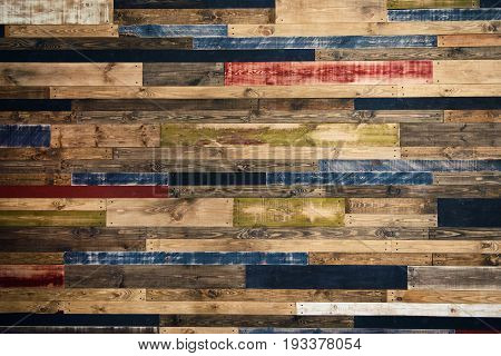 Wall made of multi-colored wooden boards. Abstract grunge wood texture background.