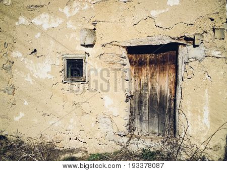 Wooden door and window on old abandoned house of clay in abandoned Serbian village.