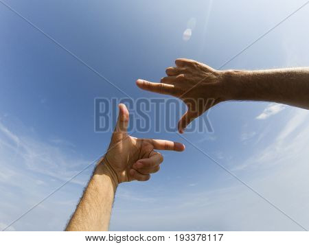 Two hands form with a fingers a frame in front of a blue sky with clouds and reflection