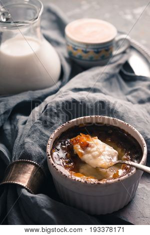 Creme brulee with cup of coffee  and jug of milk on the stone background vertical