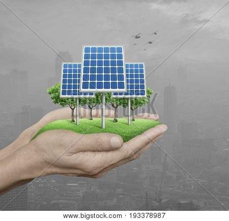 Solar cell in man hands over pollution city with birds Ecological energy concept