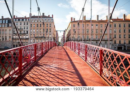 Morning view on the red footbridge and the riverside with beautiful buildings in Lyon city