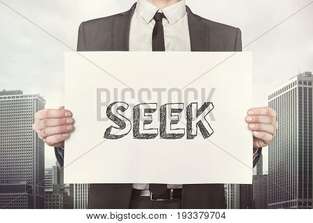 Midsection of businessman holding placard with seek text while standing against buildings