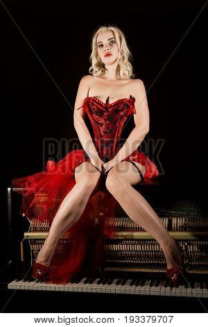 beautiful blonde musician in red corset sitting on a piano. Vintage style beautiful woman.. Old fashioned makeup and retro finger wave hairstyle.