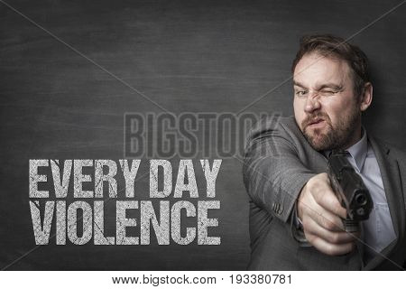 Businessman aiming handgun while standing by everyday violence text on blackboard