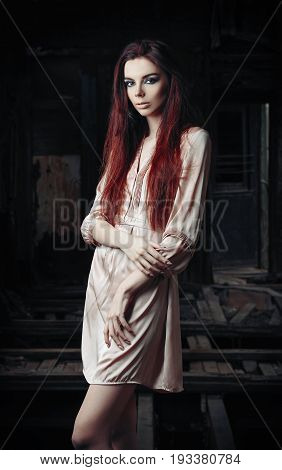 Portrait of beautiful young girl among the abandoned ruins