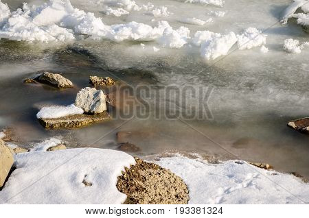 Rocks in frozen Danube river. Winter image of rocks covered by snow and ice in the water. Novi Sad, Serbia.
