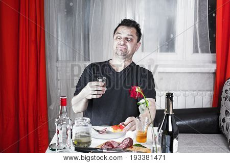 Drunk Unshaven Sad Man Sits At A Table With Drinks And Snacks, Looks At A Glass With Vodka And Frown