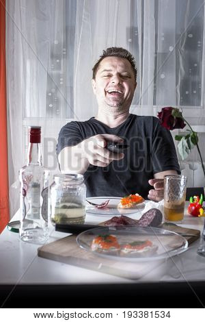 Drunk Unshaven Man Sitting At The Banquet Table With Drinks And Snacks, Laughs And Index Finger Poin