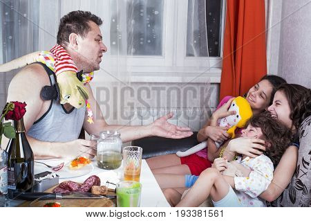 Drunk Unshaven Father Joked With His Children. He Sits At The Banquet Table With Drinks And Snacks.