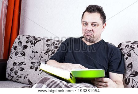 Unshaven Man Sits On A Sofa And Contemptuously Looking At The Book.