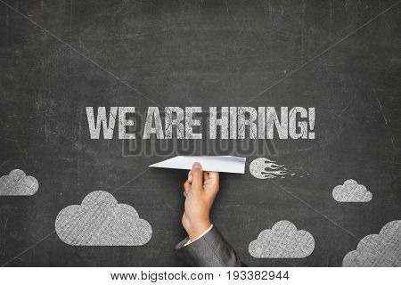 Cropped hand of businessman holding paper plane under we are hiring text on blackboard