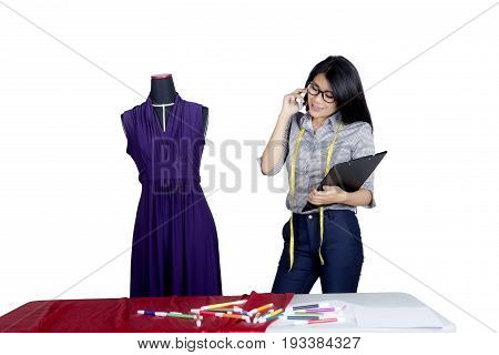 Picture of a beautiful fashion designer looks busy while speaking on a mobile and holding a clipboard on the studio