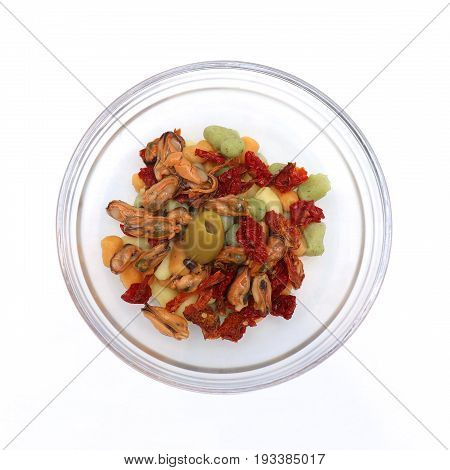 Gnocchi with clams and tomato in glass bowl on white background