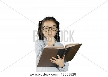 Picture of a little clever girl studying with a book while daydreaming in the studio isolated on white background