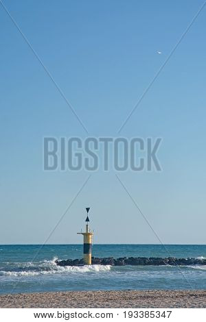 Lighthouse and airplane takeoff at Molinar beach on a sunny summer evening in Mallorca Balearic islands Spain.