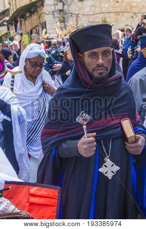 JERUSALEM - APRIL 14 : Christian pilgrim carry across along the Via Dolorosa in Jerusalem on April 14 2017 commemorating the path Jesus carried his cross on the day of his crucifixion