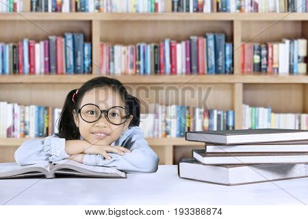 Elementary student sitting in the library with textbooks on the table while looking at the camera
