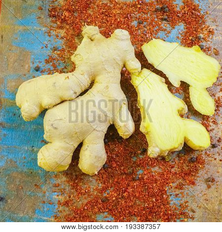 Fresh Organic Ginger Root With Powdered Cayenne Pepper On The Wooden Table