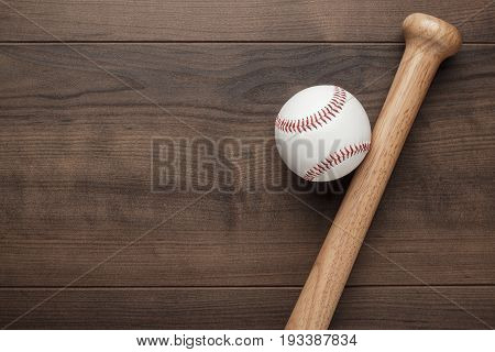 closeup of baseball bat and ball. baseball equipment on brown table. baseball gear on the wooden background. top view of baseball gear with copy space