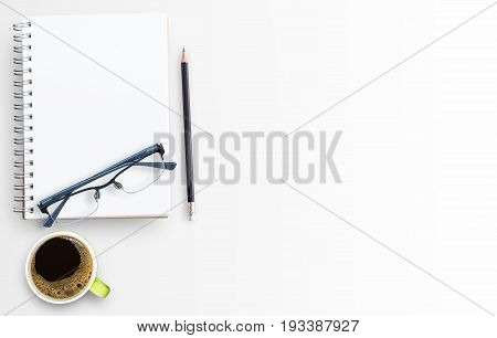 Blank paper notebook and cup of coffee on white table background. Top view with copy space (selective focus). Office desk table concept..Office supplies and gadgets on desk table.Flat lay photo.