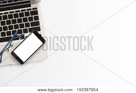 White office desk table with laptop computer smart phone notebook and eyeglasses. Top view with copy space.Business desk table concept.Office supplies and gadgets on desk table.Flat lay photo.