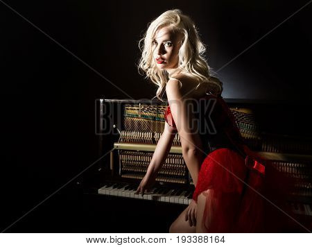 beautiful blonde musician in red corset standing near the piano. Vintage style beautiful woman.. Old fashioned makeup and retro finger wave hairstyle.