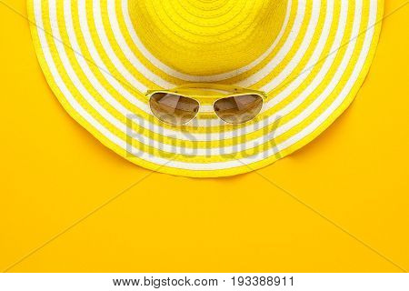 yellow sunglasses and striped retro summer hat. summer concept. summer accessories on the yellow background. summer accessories with copy space. top view of summer style accessories