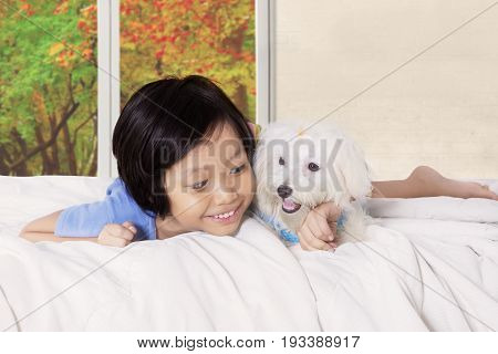 Little girl lying in the bed while hugging canine in the bedroom with autumn background on the window