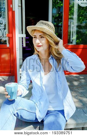 Blonde Hair Girl In Jeans Wear And Straw Hat Holding A Cup Of Aromatic Cappuccino. Teenage Lifestyle