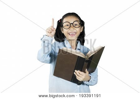 Cheerful schoolgirl getting inspiration while holding a textbook isolated on white background